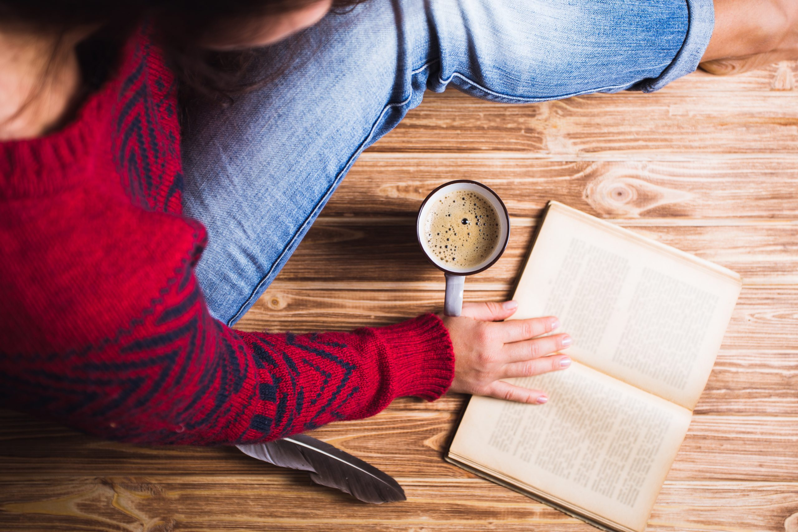 Woman reading a book with her morning coffee.