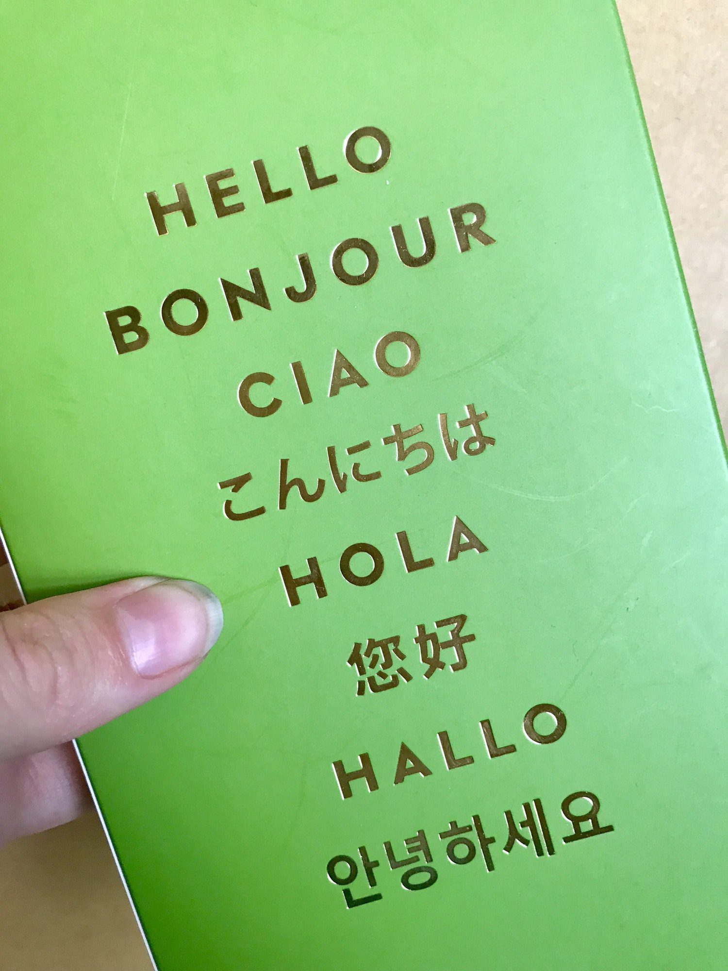 Hand holding a sign that says hello in multiple languages