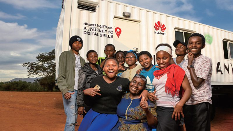 Kids posing and smiling in front of the DigiTruck with an older woman.