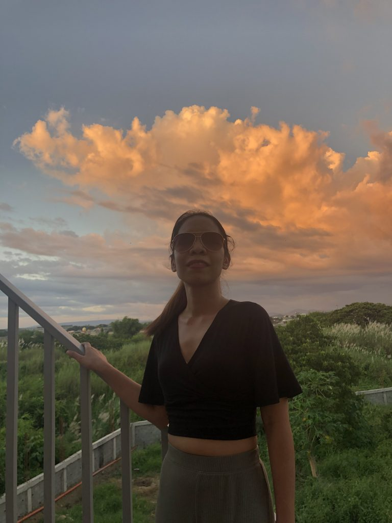 Jasmin Ambiong, smiling with a sunset background.