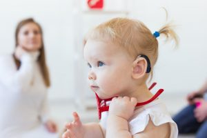 Baby girl wearing a hearing aid. Disabled child, disability and deafness concept