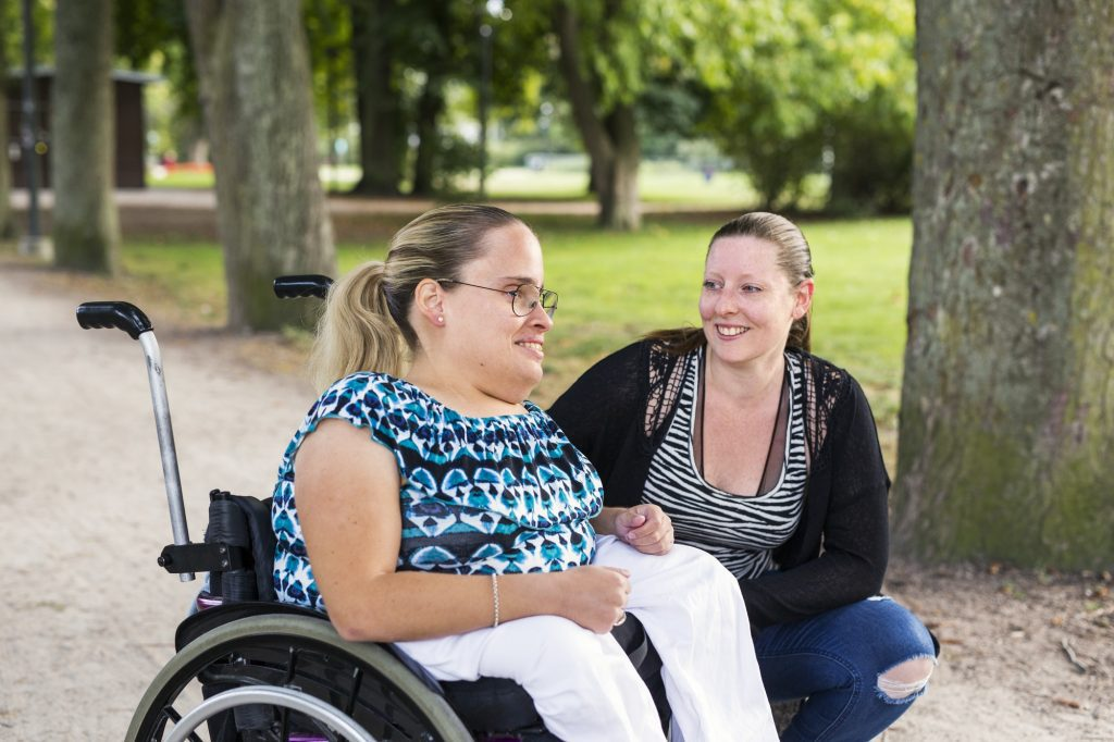 Disabled woman in wheelchair with assistant in park